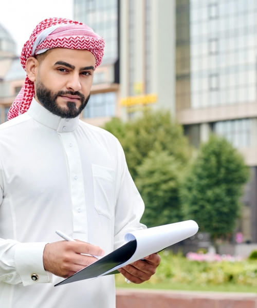 confident-arabic-businessman-looking-holding-clipboard-with-documents-min